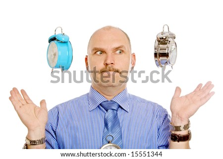 Man pulling a face while two alarm clocks are suspended above his hands - stock photo