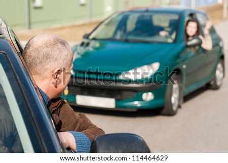 Man pulling a woman's car with problems breakdown help broken - stock photo