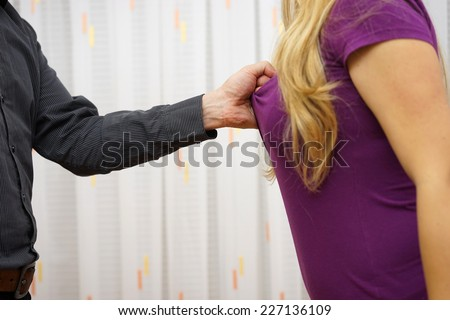 man  pulling his girlfriend's shirt, violence concept over woman - stock photo