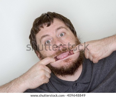 Man pulling his lips to the side and sticking his tongue out being goofy - stock photo