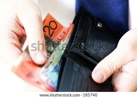 man pulling money out of wallet - stock photo