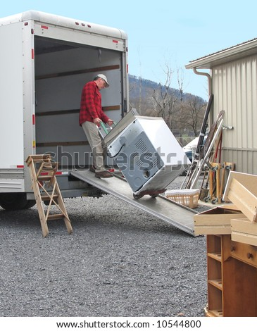 Man pulls dryer onto moving van using a dolly	 - stock photo