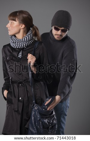 man pulls wallet out of a woman handbag - stock photo