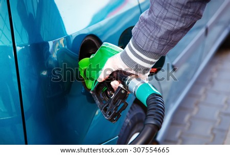 man pumping gasoline fuel in car at gas station. transportation concept .