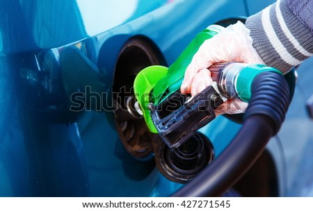 man pumping gasoline fuel in car at gas station. transportation concept.