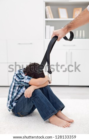 Man punishing his son with a belt - stock photo
