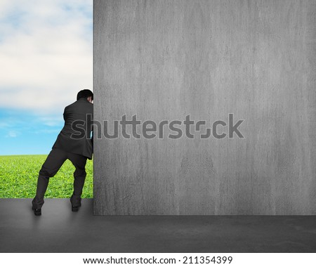 man push away concrete wall with sky and grass background - stock photo