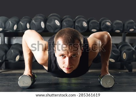 man pushed to the background of dumbbells on the rack with dumbbells - stock photo