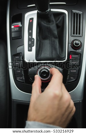 man pushes a button in the car