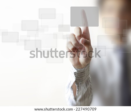 Man pushing a button on a touch screen interface - stock photo