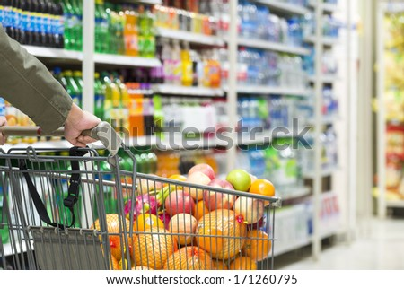 man pushing a shopping cart in the supermarket. - stock photo