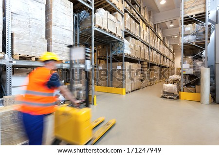 Man pushing a yellow forklift in huge store - stock photo