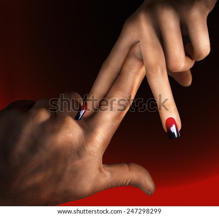 Man pushing his finger between woman's fingers with red and black ombre nails in a dark background - stock photo