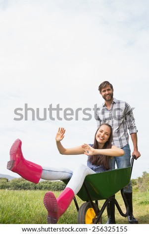 Man pushing his girlfriend in a wheelbarrow on a sunny day - stock photo