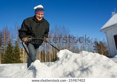 Man pushing snow - stock photo