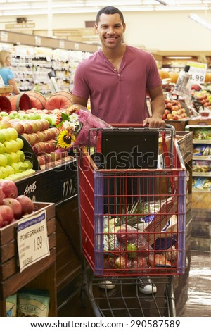 Man Pushing Trolley By Fruit Counter In Supermarket - stock photo