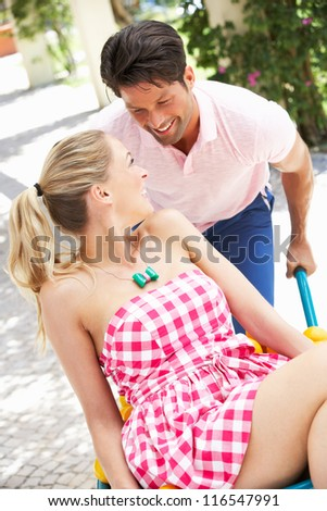 Man Pushing Woman In Wheelbarrow Filled With Oranges - stock photo
