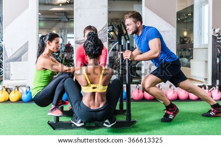 Man pushing women on cart as fitness exercise in gym - stock photo
