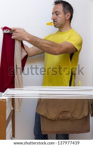 Man put washing on drying rack - stock photo