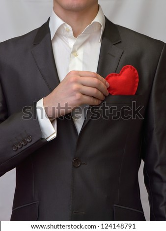 Man puts a red decorative heart in pocket - stock photo