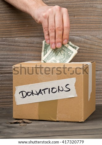 Man puts dollar bills into donation carton box with coins on wooden table background