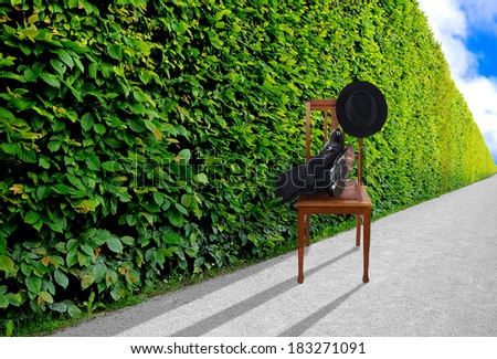 Man puts his feet up in endless hedge - pausing concept - stock photo