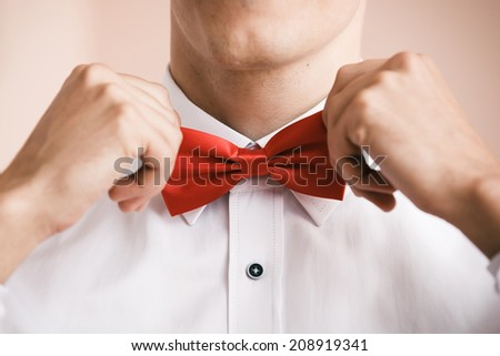 Man puts on red bow tie. Close up. Shallow depth of field. Focused on  bow tie. - stock photo