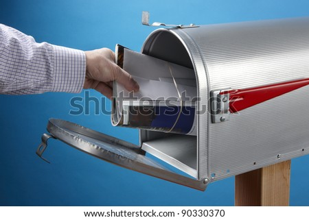 Man puts or takes out mail at an open mailbox - stock photo