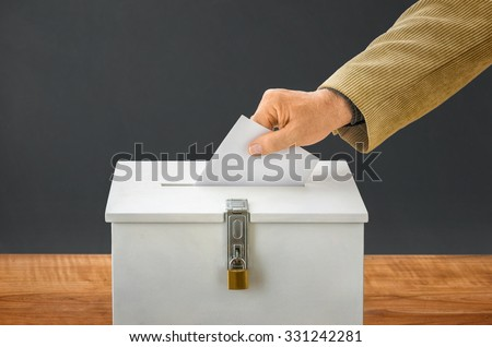 Man putting a ballot into a voting box  - stock photo