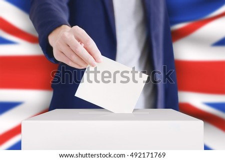 Man putting a ballot into a voting box with British flag on background.