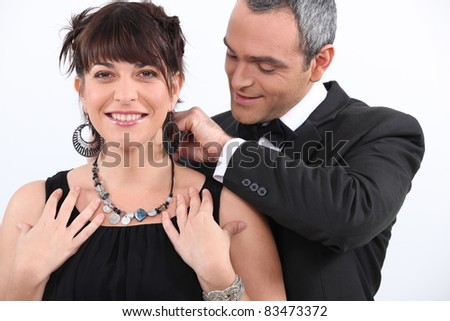 Man putting a necklace on his lover - stock photo