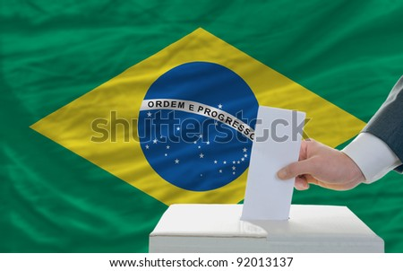man putting ballot in a box during elections in brazil - stock photo