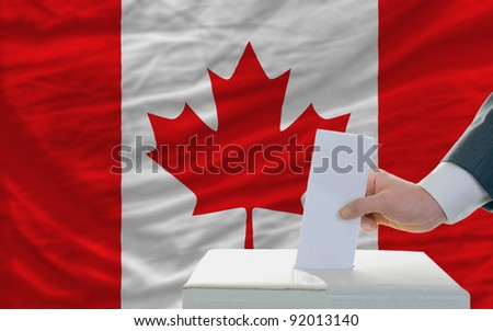 man putting ballot in a box during elections in canada - stock photo