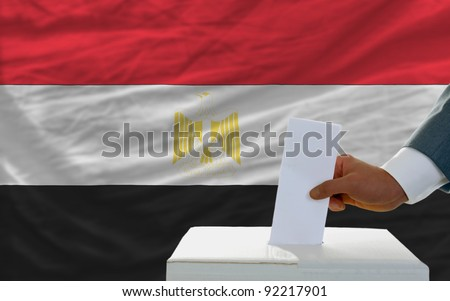 man putting ballot in a box during elections in egypt in front of flag - stock photo