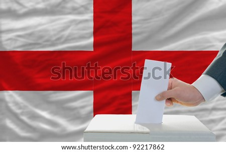 man putting ballot in a box during elections in england in front of flag