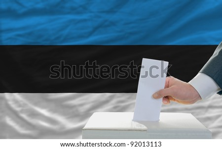 man putting ballot in a box during elections in estonia - stock photo