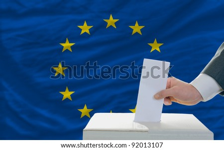 man putting ballot in a box during elections in european union - stock photo