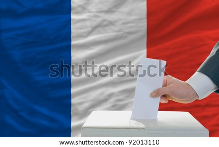 man putting ballot in a box during elections in france - stock photo