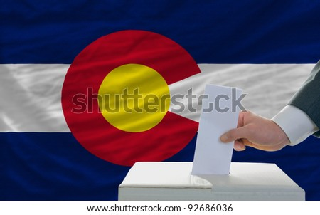 man putting ballot in a box during elections  in front of flag american state of colorado - stock photo