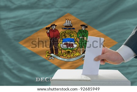 man putting ballot in a box during elections  in front of flag american state of delaware - stock photo