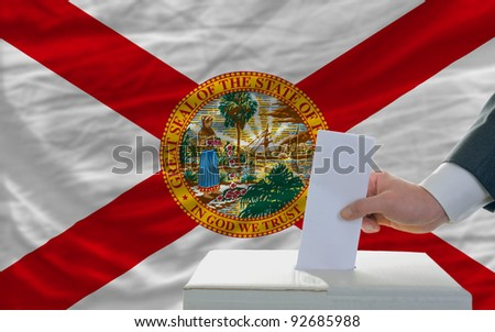 man putting ballot in a box during elections  in front of flag american state of florida - stock photo
