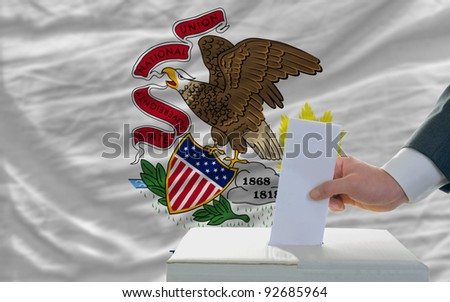 man putting ballot in a box during elections  in front of flag american state of illinois - stock photo
