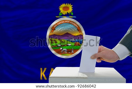 man putting ballot in a box during elections  in front of flag american state of kansas - stock photo