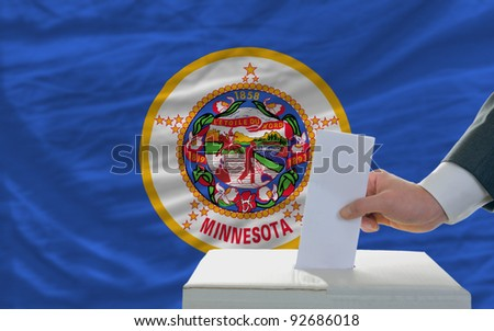 man putting ballot in a box during elections  in front of flag american state of minnesota - stock photo