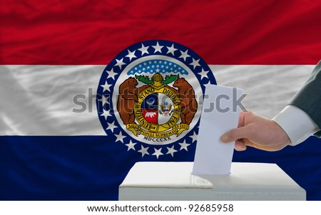 man putting ballot in a box during elections  in front of flag american state of missouri - stock photo