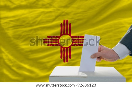 man putting ballot in a box during elections  in front of flag american state of new mexico - stock photo