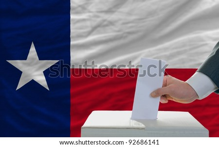 man putting ballot in a box during elections  in front of flag american state of texas - stock photo