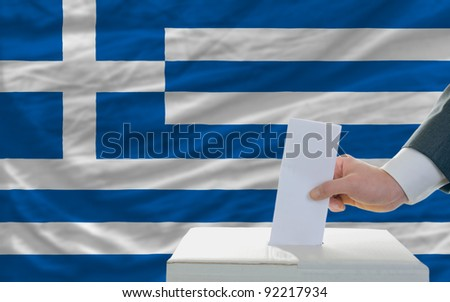 man putting ballot in a box during elections in greece in front of flag - stock photo