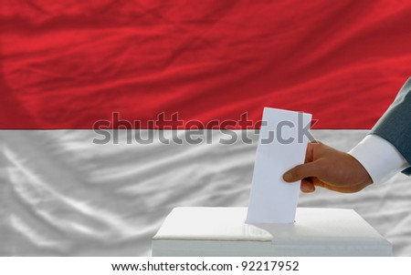 man putting ballot in a box during elections in indonesia in front of flag - stock photo