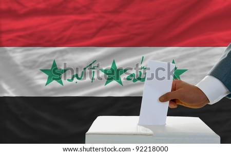 man putting ballot in a box during elections in iraq in front of flag - stock photo